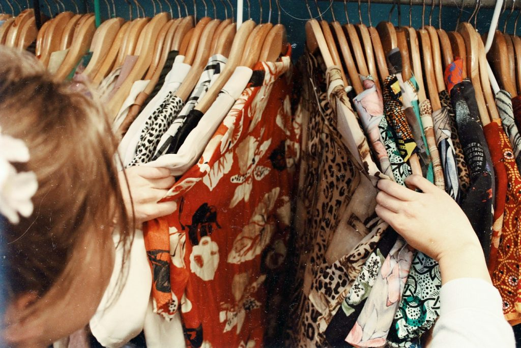 Woman selecting clothes on rack in shop